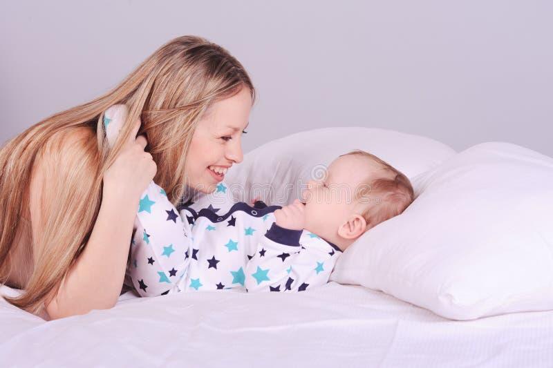 Mulher de sorriso que encontra-se na cama com bebê fotografia de stock royalty free