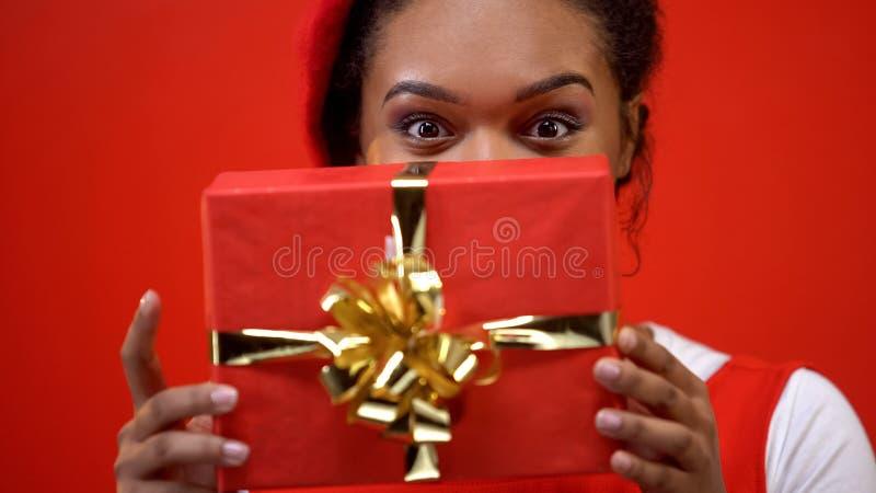 Mulher de sorriso que esconde atrás da caixa de presente vermelha, preparando o dia de Valentim atual do St foto de stock