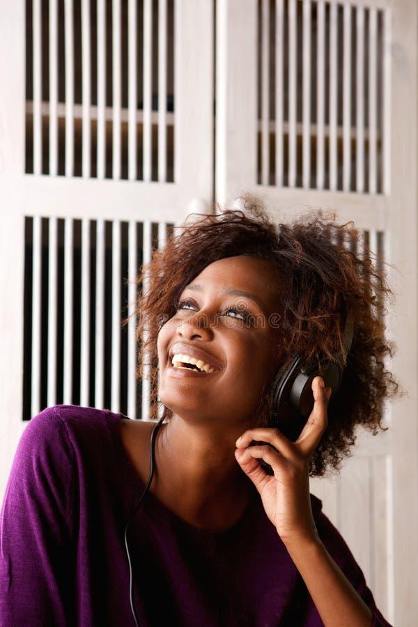 Mulher de sorriso que escuta a música em fones de ouvido foto de stock