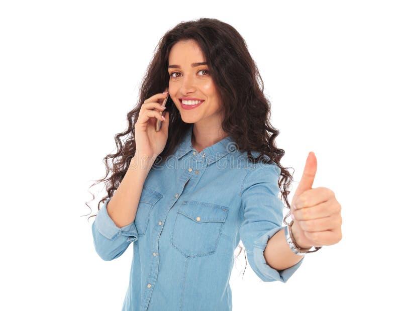 Mulher de sorriso que fala no telefone e que faz está bem foto de stock royalty free