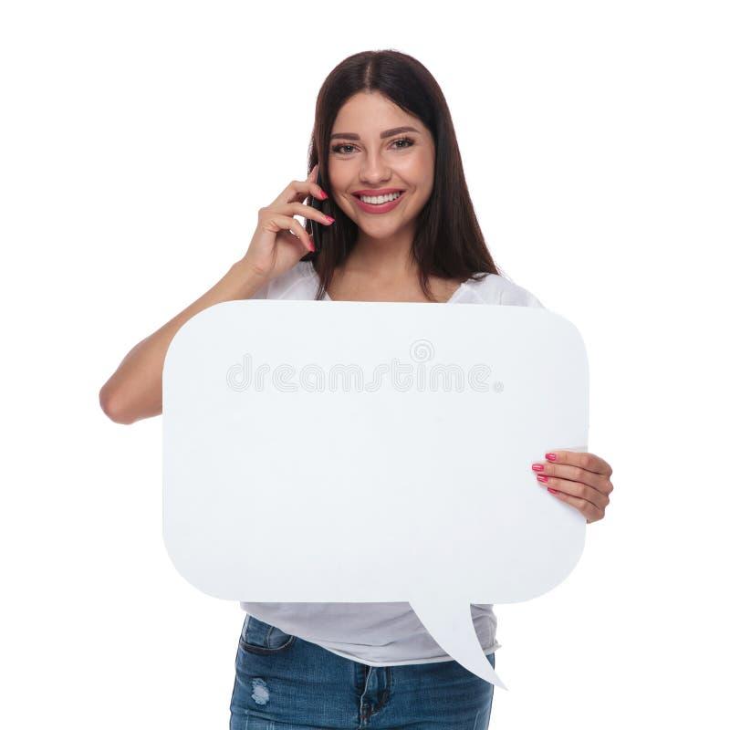 A mulher de sorriso que fala no telefone guarda a bolha do discurso imagens de stock royalty free