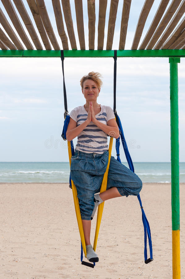 Mulher de sorriso que faz a ioga aérea antigravitante na praia Ioga da mosca no asana, namaste foto de stock