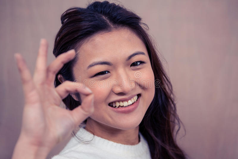 Mulher de sorriso que faz o sinal aprovado com mão foto de stock