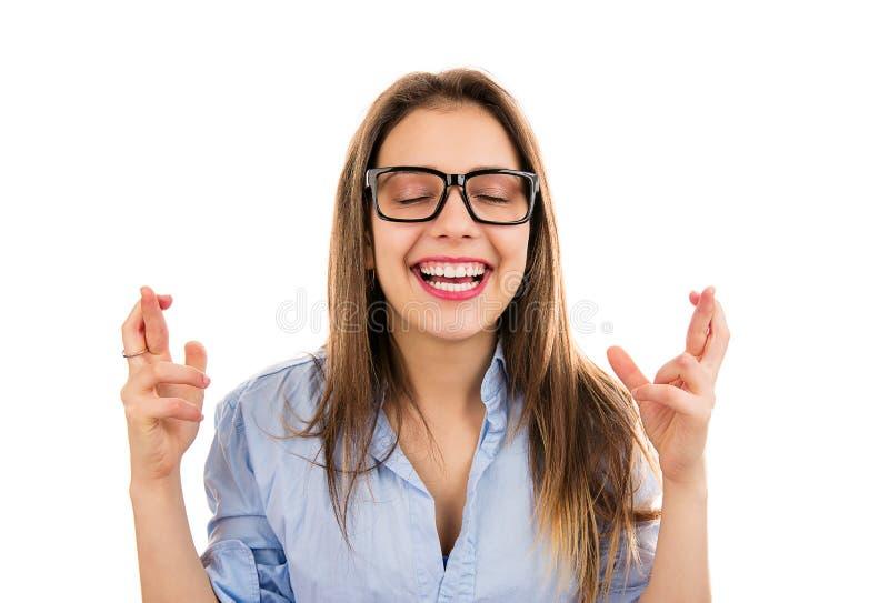Mulher de sorriso que faz um desejo com dedos cruzados foto de stock royalty free