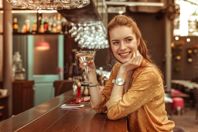 Mulher de sorriso que guarda a bebida de martini que senta-se no contador da barra imagens de stock royalty free
