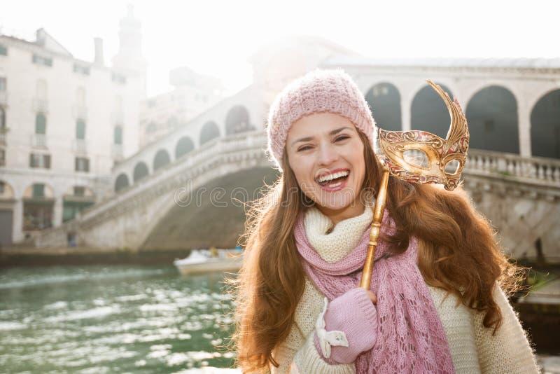 Mulher de sorriso que guarda a máscara de Veneza na parte dianteira da ponte de Rialto fotos de stock royalty free