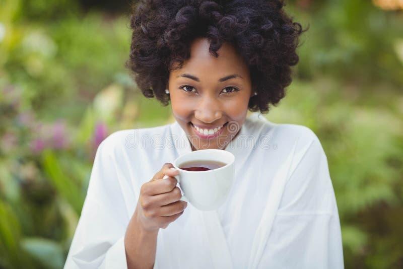 Mulher de sorriso que guarda o chá fotos de stock