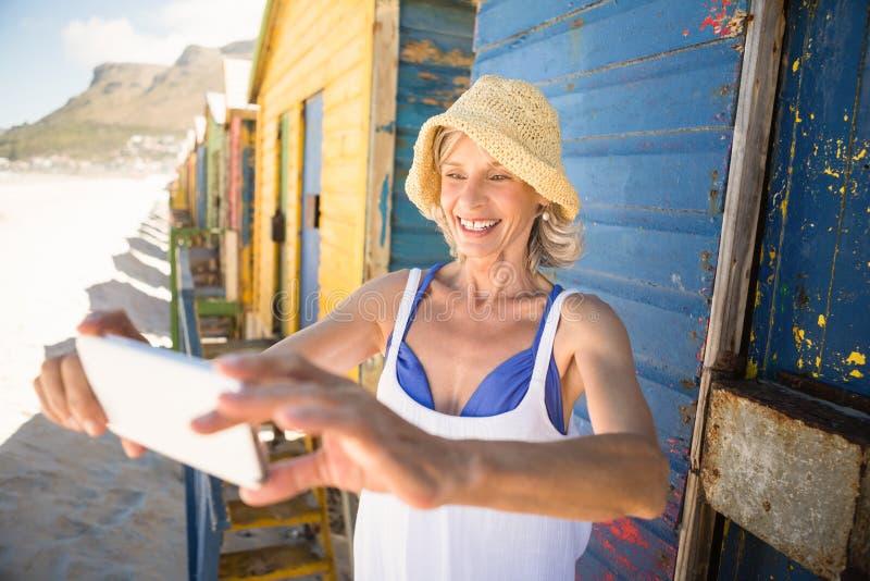Mulher de sorriso que guarda o telefone celular ao estar contra a parede fotos de stock