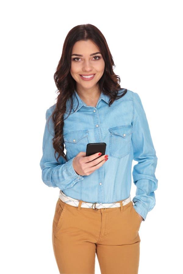 Mulher de sorriso que guarda o telefone e texting foto de stock