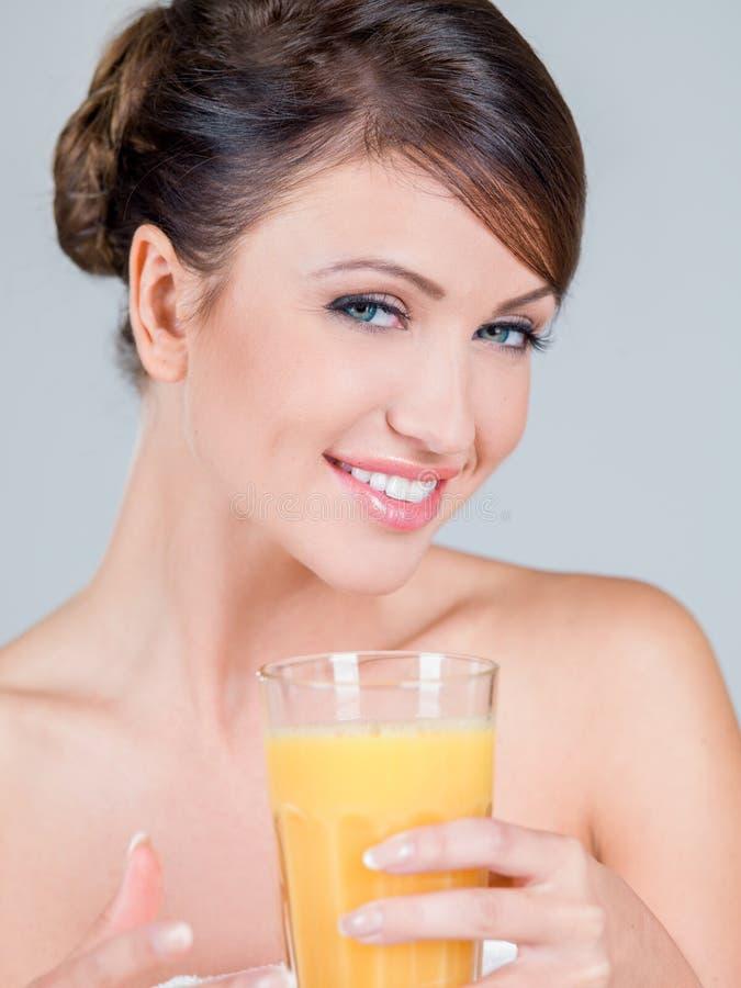 Mulher de sorriso que guarda o vidro do suco de laranja fotos de stock