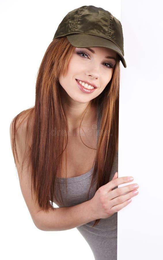 Mulher de sorriso que inclina-se na placa em branco foto de stock