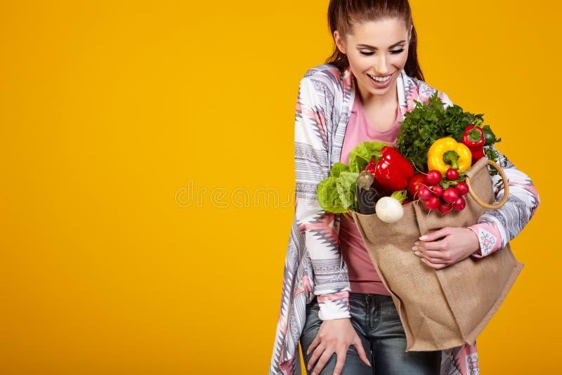 Mulher de sorriso que leva um saco com vegetais fotografia de stock royalty free