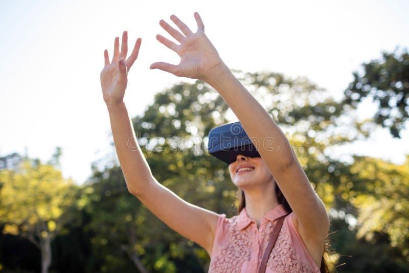 Mulher de sorriso que levanta suas mãos ao usar uns auriculares de VR no parque foto de stock royalty free
