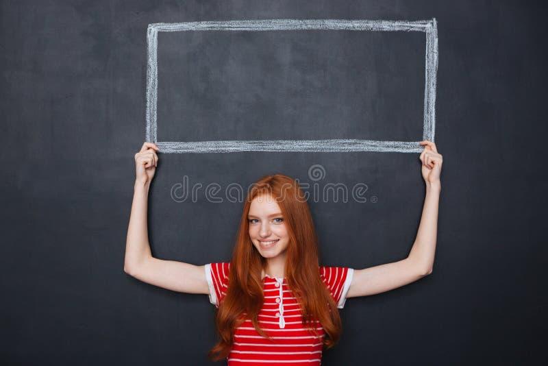 Mulher de sorriso que mantém o quadro tirado no quadro-negro acima de sua cabeça imagem de stock royalty free