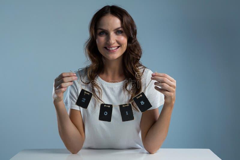 Mulher de sorriso que mantém um cartão de 2018 contra o fundo branco imagem de stock royalty free