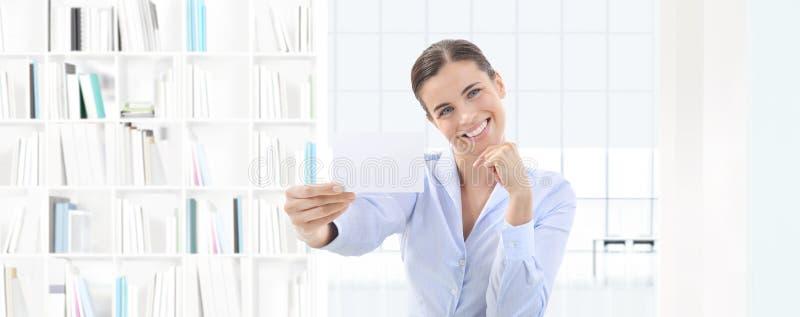 Mulher de sorriso que mostra o cartão em sua mão no offi interior imagens de stock royalty free