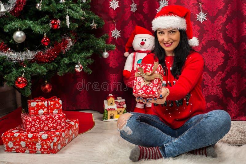 Mulher de sorriso que mostra o presente do Natal fotografia de stock