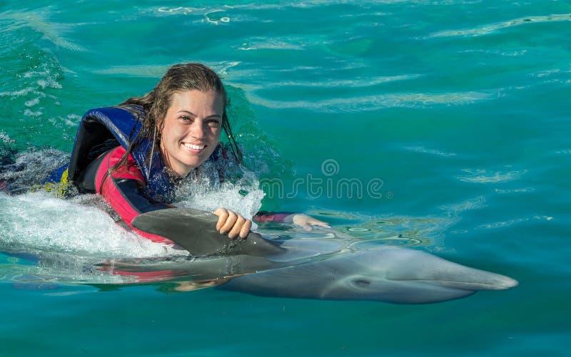 Mulher de sorriso que nada com golfinho imagem de stock royalty free