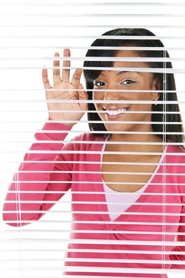 Mulher de sorriso que olha através das cortinas imagens de stock royalty free