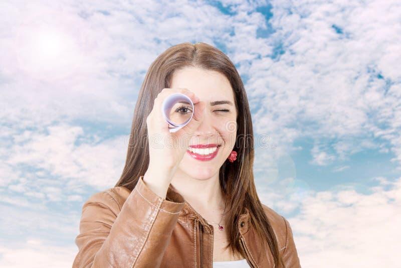 Mulher de sorriso que olha em um telescópio pequeno feito com um rolo imagem de stock royalty free