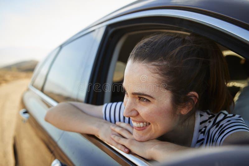 Mulher de sorriso que olha fora da janela de carro que aprecia a viagem por estrada foto de stock