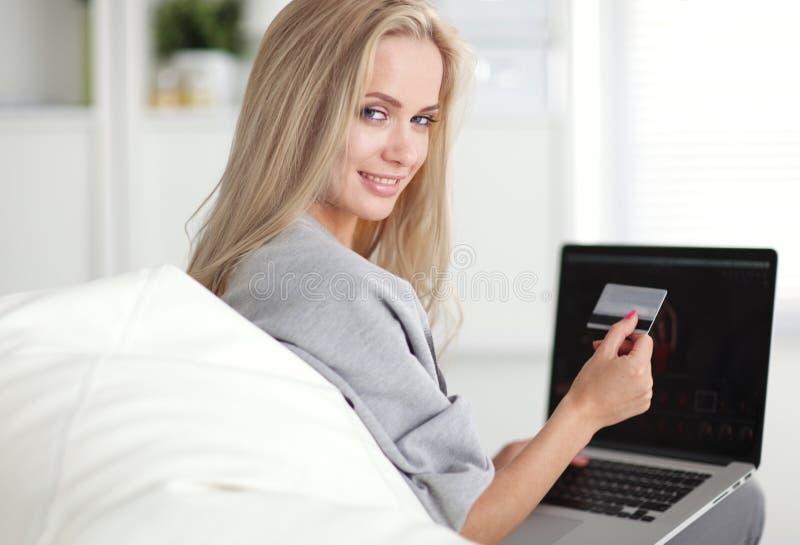 Mulher de sorriso que paga pela compra em linha com cartão imagem de stock