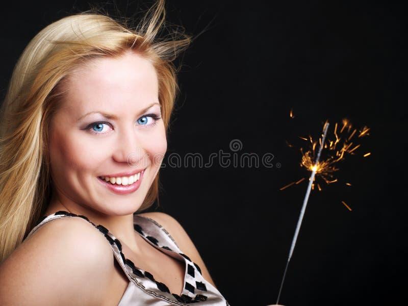 Mulher de sorriso que prende o sparkler de ano novo fotos de stock