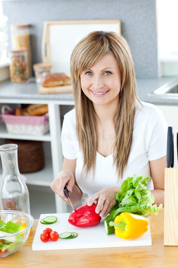 Mulher de sorriso que prepara uma salada na cozinha fotografia de stock