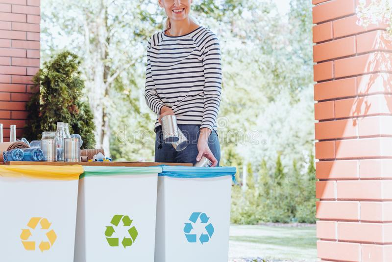 Mulher de sorriso que recicla o desperdício imagem de stock