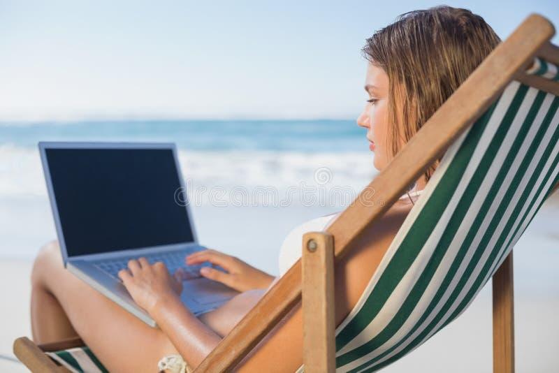 Mulher de sorriso que relaxa na cadeira de plataforma na praia usando o portátil imagens de stock royalty free