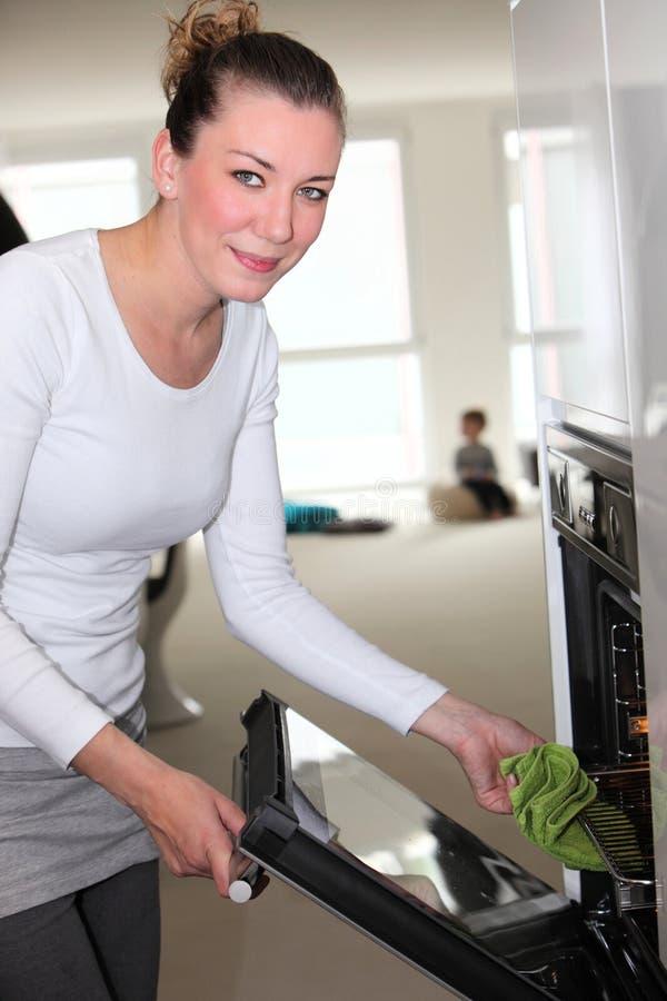 Mulher de sorriso que remove uma bandeja quente do forno fotografia de stock