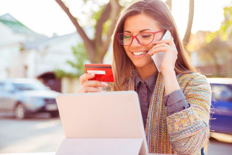 Mulher de sorriso que senta fora a fala no telefone celular que faz o pagamento em linha em seu tablet pc imagem de stock