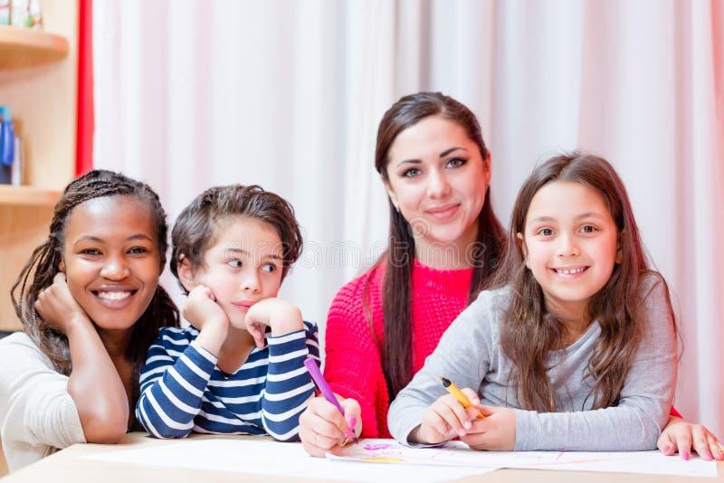 Mulher de sorriso que senta-se com crianças fotografia de stock royalty free