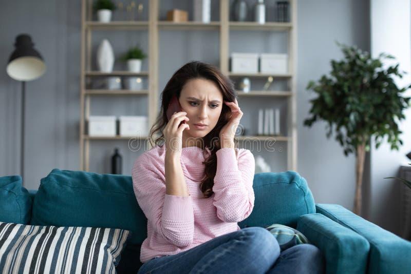 Mulher de sorriso que senta-se no sofá na sala de visitas que tem um telefonema fotos de stock royalty free