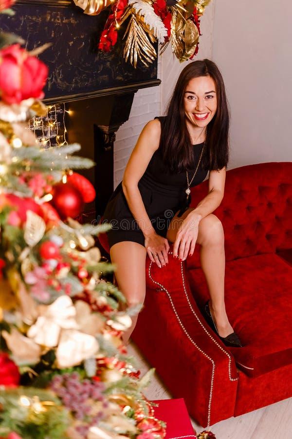 Mulher de sorriso que senta-se no sofá vermelho para o Natal Mulher moreno e árvore de Natal Mulher no vestido curto preto que ol imagens de stock royalty free