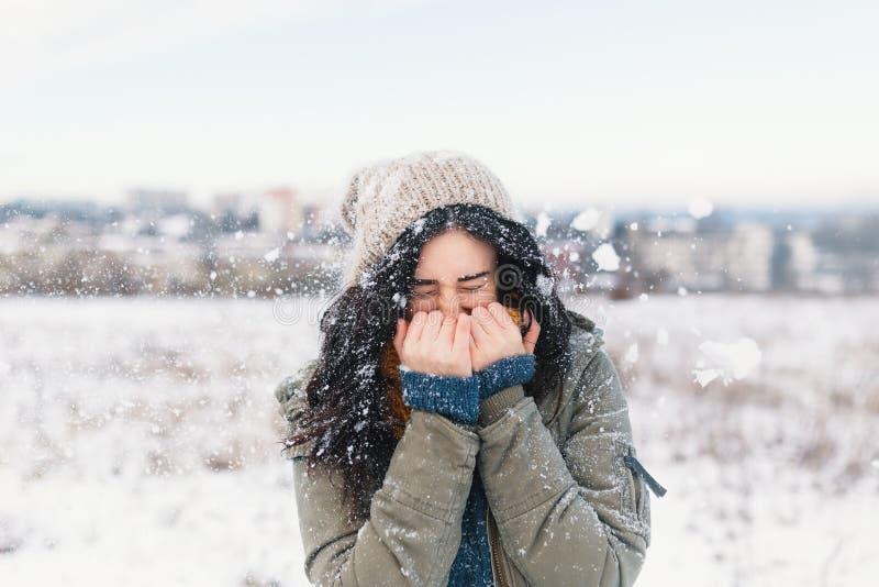 Mulher de sorriso que sente flocos de neve frios em sua cara durante uma neve fotos de stock royalty free