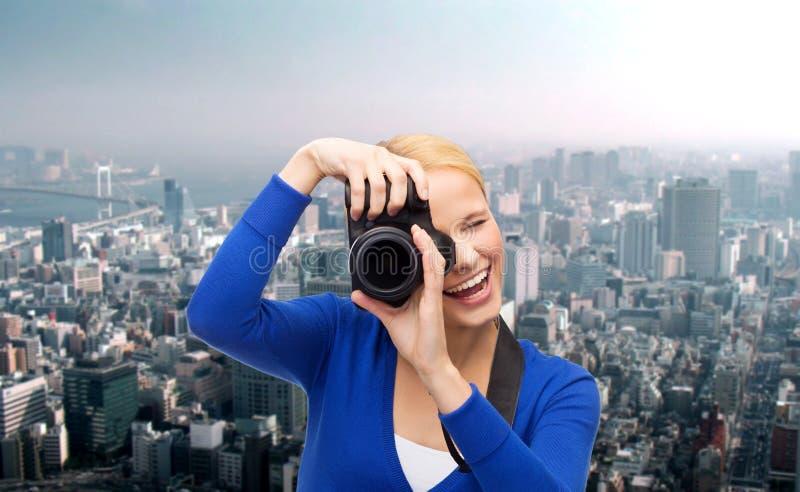 Mulher de sorriso que toma a imagem com câmara digital foto de stock royalty free