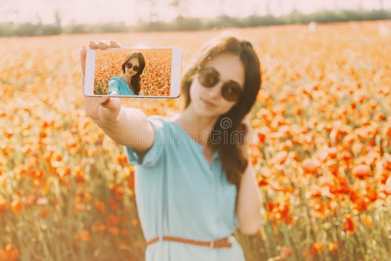 Mulher de sorriso que toma um selfie da foto com o smartphone no campo de flores fotografia de stock