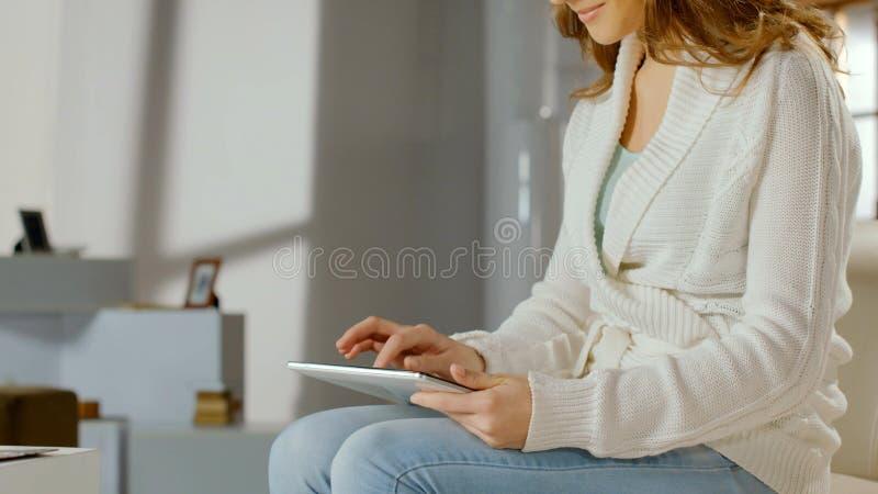 Mulher de sorriso que usa o app no PC da tabuleta em casa, conversando em linha, filmes de observação foto de stock