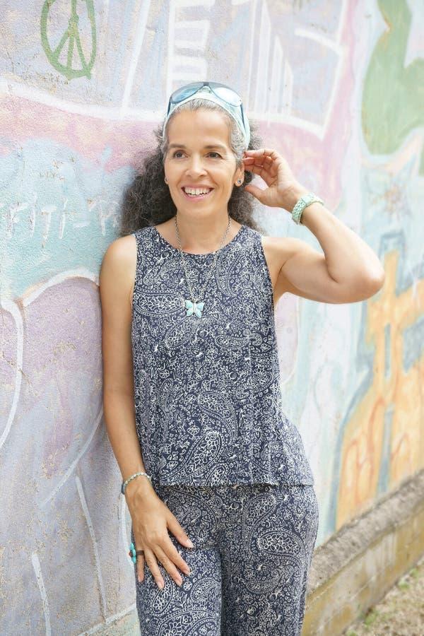 Mulher de sorriso sobre 50 que inclinam-se na parede dos grafittis fotografia de stock royalty free
