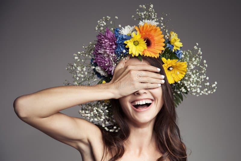 Mulher de sorriso surpreendida com a grinalda da flor em sua cabeça foto de stock