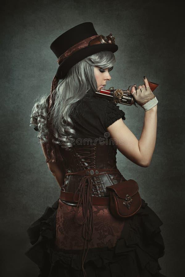 Mulher de Steampunk com arma mecânica imagem de stock