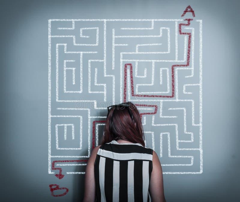 A mulher de Thoughful está considerando como encurtar o trajeto através do labirinto imagem de stock royalty free
