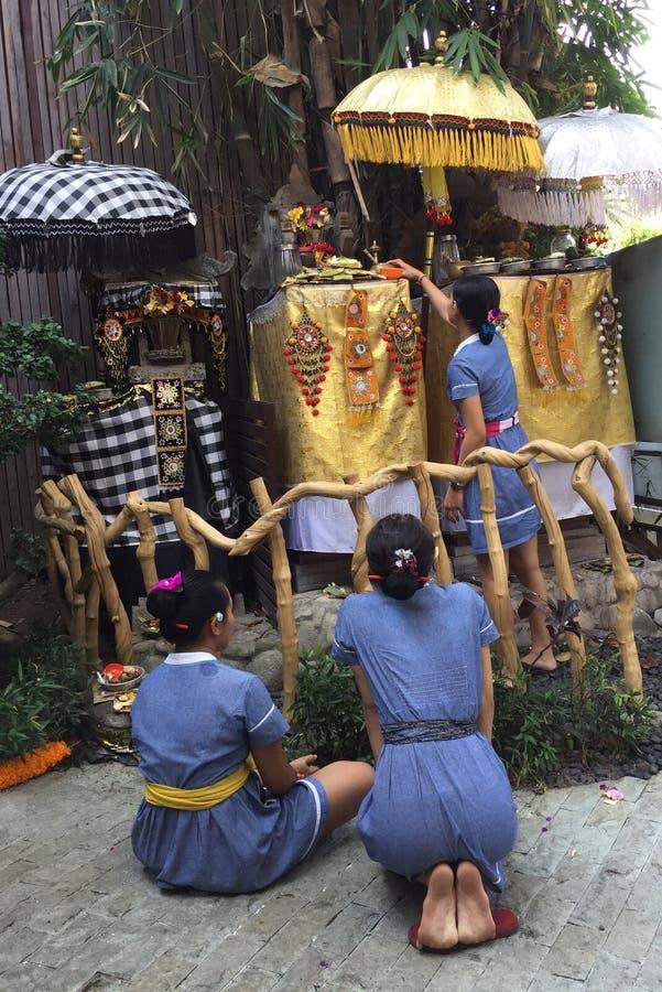 Mulher de três balinese na frente do santuário pequeno para a oração fotos de stock