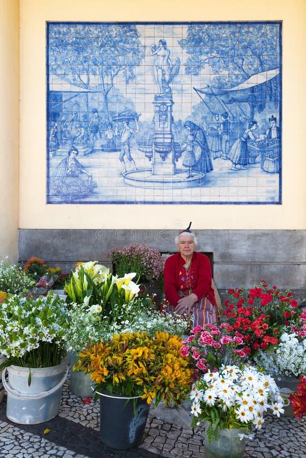 A mulher de Ttraditional vende flores em um mercado de Funchal, Portugal fotografia de stock royalty free