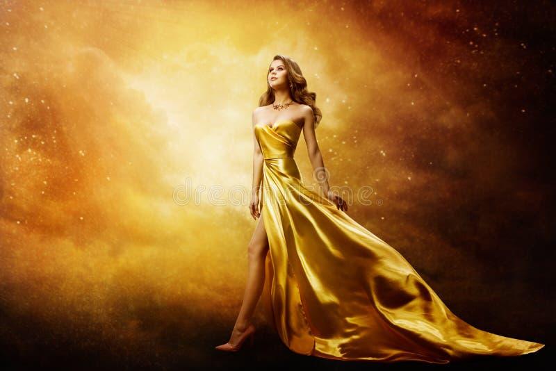 Mulher de Vestido Dourado procurando por estrelas espaciais, um belo modelo de moda no céu dourado foto de stock royalty free