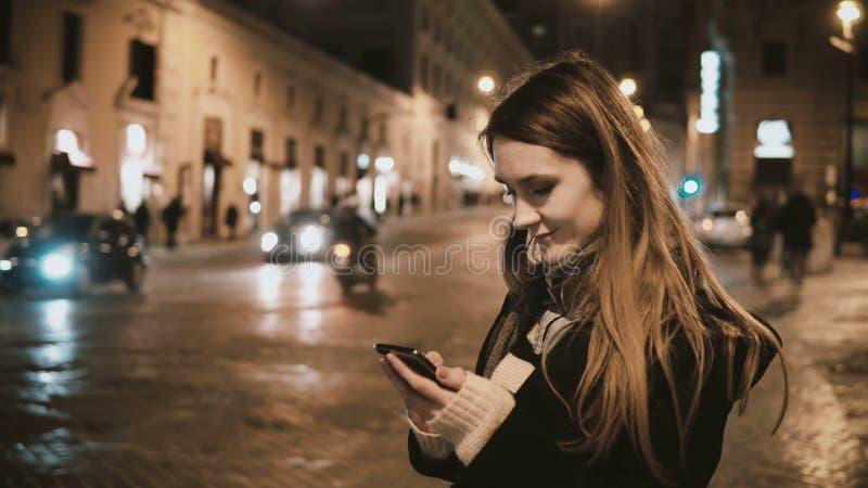 Mulher de viagem nova que anda no centro de cidade na noite e que usa o smartphone, tentativa para encontrar a maneira e para par fotografia de stock royalty free
