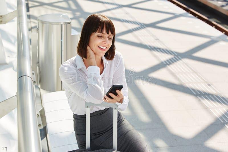 Mulher de viagem que espera no terminal com bagagem e o telefone esperto fotografia de stock