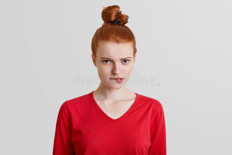 A mulher de vista agradável descontentada do gengibre com os bordos das curvas do nó do cabelo no descontentamento, tem a express fotos de stock royalty free