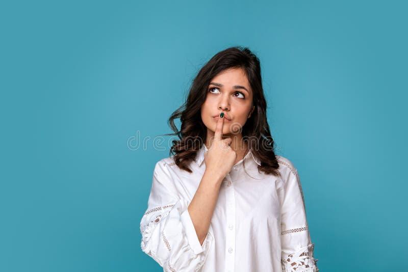 Mulher de Youn em uma pose de pensamento isolada sobre o fundo azul fotografia de stock